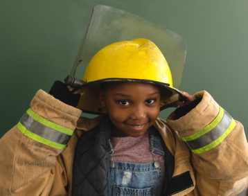 Young girl in firefighter jacket and helmet