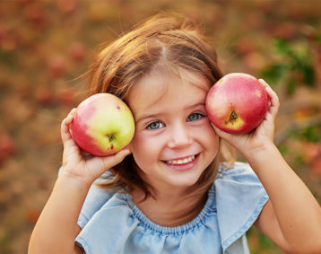 Happy young girl while picking apples