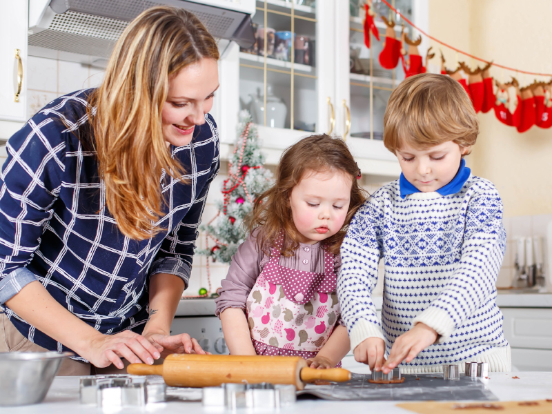 Mom baking christmas cookies with her kids