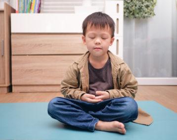 Young Asian boy meditating