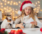 Girl making Christmas crafts with her dog watching