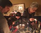 family lighting Menorahs