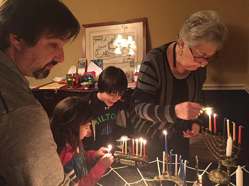 family lighting Menorahs